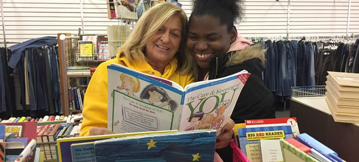 "Two women reading a book titled, ""The Care & Keeping of You"" at Goodwill."