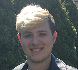 A young adult with blonde hair and a black leather jacket stands in front of pine trees.